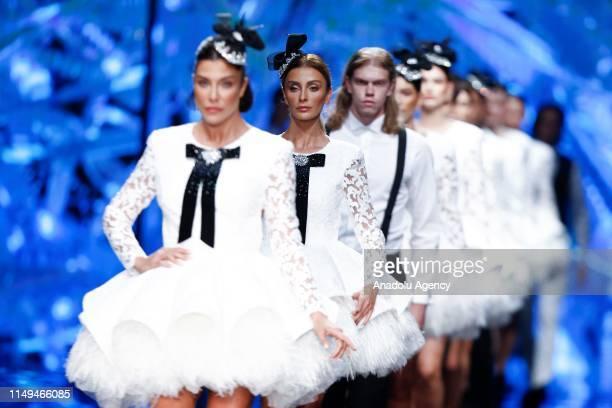 Models, along with Turkish models Deniz Akkaya and Ozge Ulusoy walk on runway at Dosso Dossi Fashion Show in Antalya, Turkey on June 12, 2019.