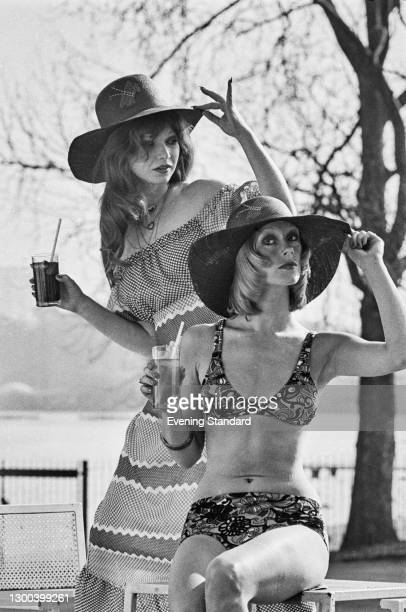 Models Annette and Helga wearing wide-brimmed hats and summer outfits, UK, 16th March 1973.