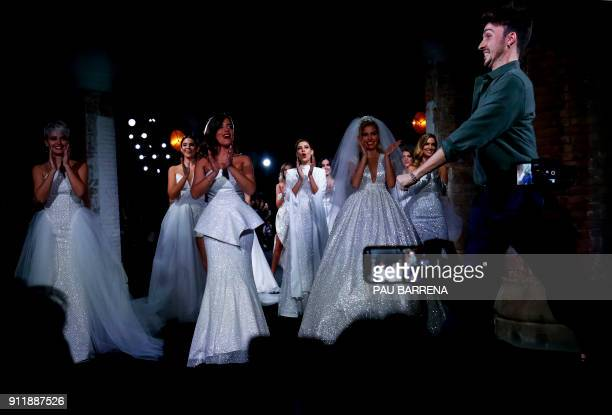TOPSHOT Models applaud as Spanish designer Jose Maria Garcia appears on the catwalk following the presentation of Ze Garcia collection during the 080...