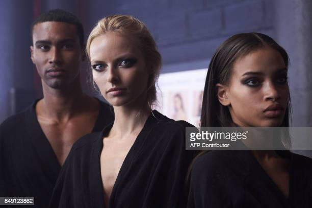 TOPSHOT Models are prepared by stylists backstage ahead of the catwalk show by British designer Julien Macdonald during a catwalk show for the...