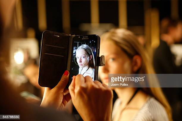Models are taking selfies with their phone backstage ahead of the Wataru Tominaga presented by MercedesBenz Elle show during the MercedesBenz Fashion...