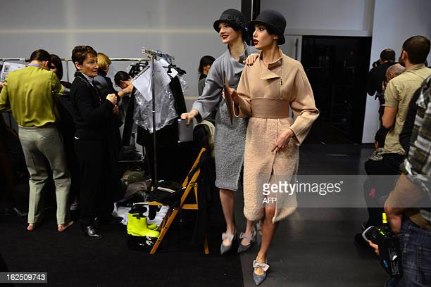 Models arrive backstage after walking on the catwalk during the Emporio Armani FallWinter 20132014 Womenswear collection on February 24 2013 during...