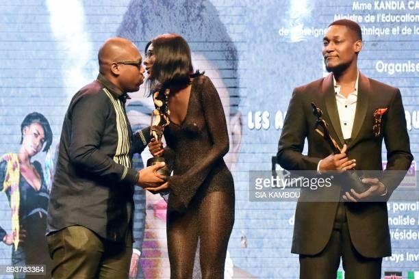 Models Awa Sanoko and Tony Santana receive an award during the 8th African Model Exhibition Awards on December 15 in Abidjan / AFP PHOTO / SIA KAMBOU
