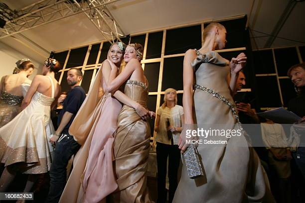 Models behind the scenes before the parade carrying models of the haute couture line 'Private' by Giorgio Armani dresses and suits with marrying...