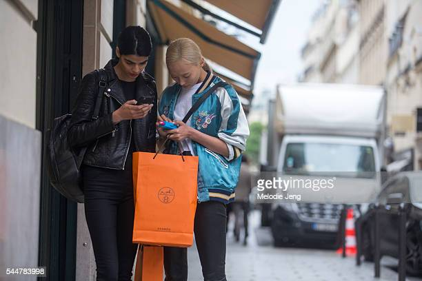 Models Bhumika Arora Li Xiao Xing check their phone at the Hermes presentation on July 3 2016 in Paris France