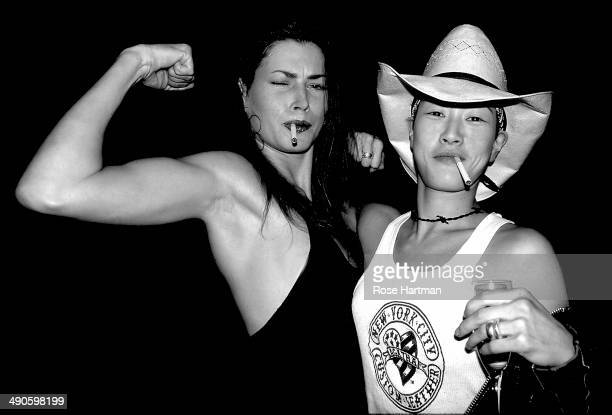 Models Carre Otis and Jenny Shimuzu vamp it up during Vogue Magazine's 'Snaps' party at an unidentified Soho loft New York New York 1990s