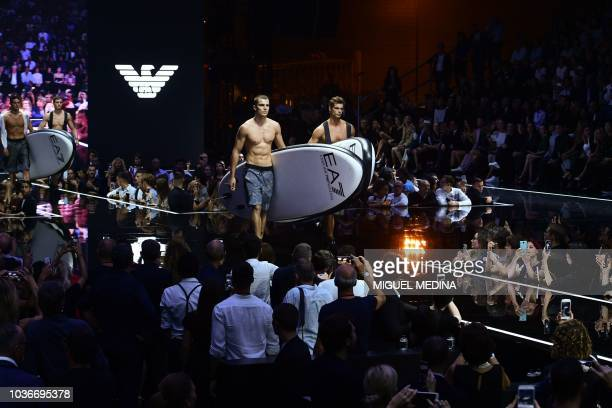 Models carrying stand up paddles walk through the runway during the presentation of the Emporio Armani fashion house collection as part of the...