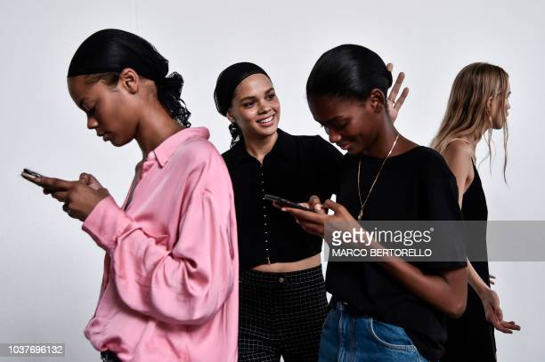 Models check their mobile phone as they wait in the backstage before the Philosophy di Lorenzo Serafini fashion show, as part of the Women's...