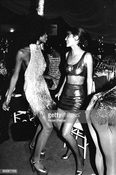 Models Christy Turlington bewigged Naomi Campbell dancing the glitter bug in skimpy outfits at 7th Ave on Sale AIDS benefit