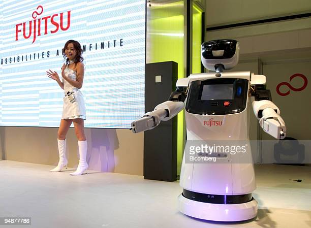 Models demonstrate modern office technology with a Fujitsu Ltd robot at Ceatec Japan Tuesday October 5 2004 in Tokyo Japanese electronics makers are...