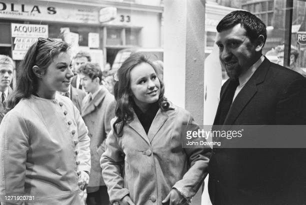 Models Diane James and Jina Baker with entrepreneur Henry Moss , whilst staging a publicity stunt in the window of Lady Jane, Moss's new boutique on...