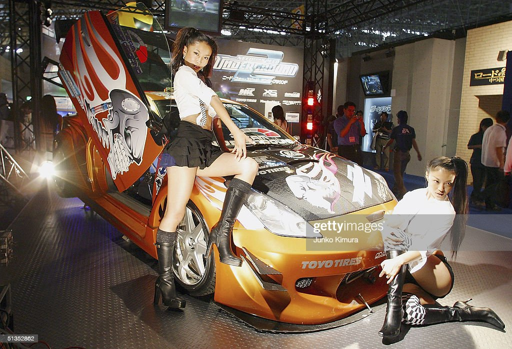 Models display a car to promote the game