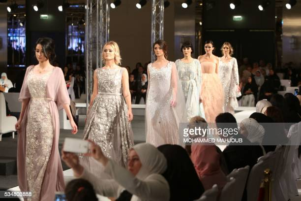 Models display creations by Omani designer Buthaina alZadjali during the launch of the 4th edition of the Ladies a La Mode fashion show on May 27 in...