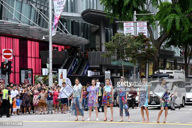 """Models display retail fashion as they stand along the crossing of the traffic junction at Orchard Road during the launch of the """"Great Singapore..."""
