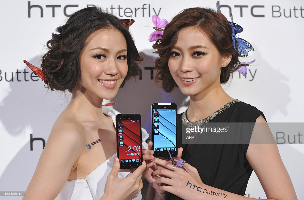 Models display Taiwan's electronics giant HTC's new smartphone 'HTCJ butterfly' during a press conference in Taipei on December 11, 2012. The new smartphone has a quad-core CPU, 5-inch sized high-definition LCD display and an 8 mega-pixel CMOS camera. AFP PHOTO / Mandy CHENG
