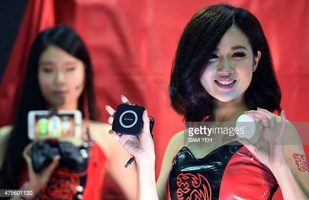Models display wireless chargers made by Thermaltake during the Computex trade show in Taipei on June 2, 2015. More then 5,000 booths from 1,700...