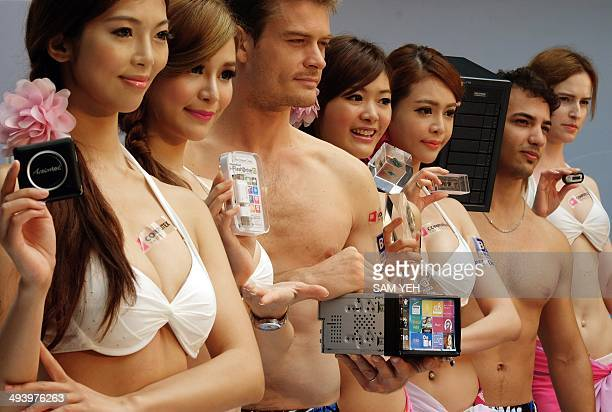 Models dressed in swimsuits display the latest information technology devices during a press conference to promote the coming Computex show in Taipei...