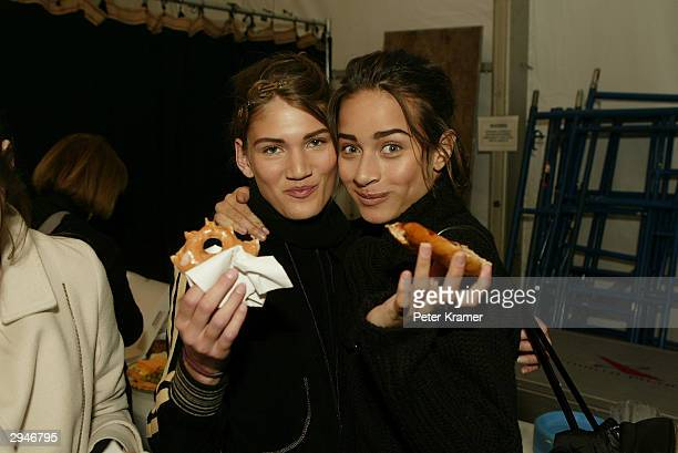 Models eat donuts and bagels as they get ready backstage at the Alice Roi fashion show during Olympus Fashion Week at Bryant Park February 8 2004 in...