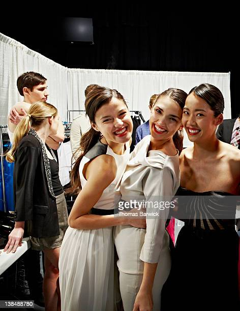 Models embracing backstage after fashion show