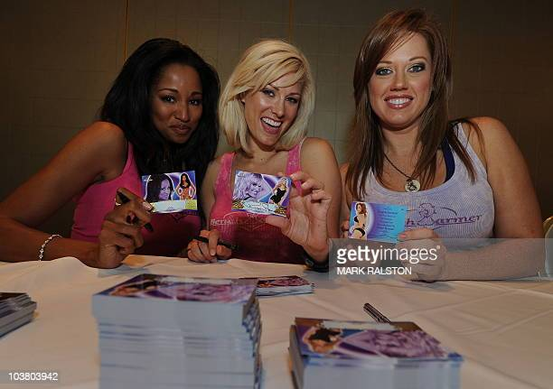 Models Enya Flack Renee Stone and Amber Strauser show their autographed Bench Warmer trading cards during a signing session in West Hollywood on...