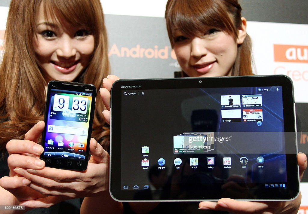 Models for KDDI Corp. pose with a Motorola XOOM tablet device manufactured by Motorola mobility Inc., right, and an htc EVO WiMAX smartphone manufactured by HTC Corp., during an unveiling in Tokyo, Japan, on Monday, Feb. 28, 2011. KDDI is Japan's second-largest mobile-phone operator. Photographer: Haruyoshi Yamaguchi/Bloomberg via Getty Images