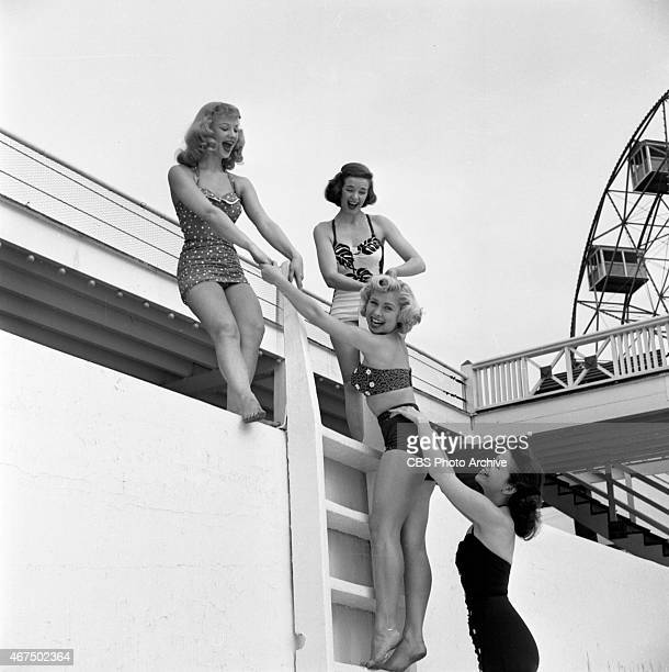 Models from the CBS gameshow The Big Payoff Connie Mavis Pat Conway Cindy Robbins and Marion James climbing a ladder at the Steeplechase Park pool in...