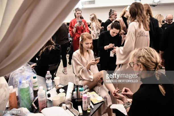 Models get prepared in the backstage prior to the Blumarine women's Fall/Winter 2019/2020 collection fashion show, on February 22, 2019 in Milan.