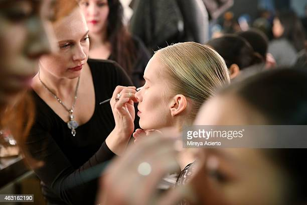 Models gets makeup applied backstage at the Epson Digital Couture presentation during MercedesBenz Fashion Week Fall 2015 at Industria Studios on...