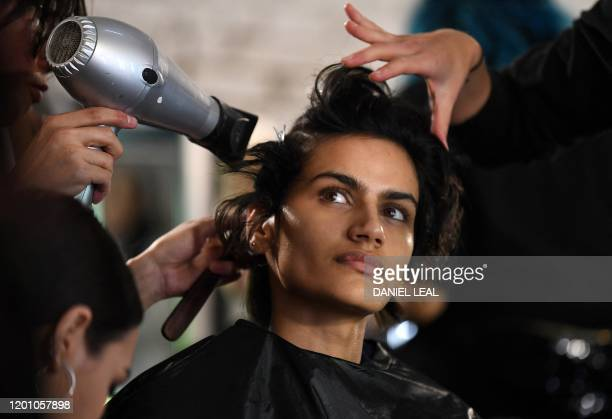 Models have their hair and make-up prepared before presenting creations by fashion house Rejina Pyo during the catwalk show for their Autumn/Winter...