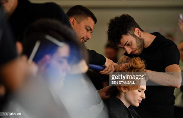 Models have their hair and make-up prepared before presenting creations by fashion house Richard Quinn during the catwalk show for their...