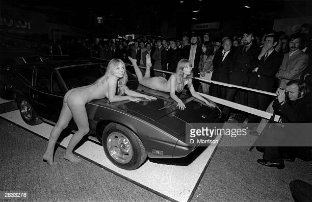 Models Helen Jones and Sue Shaw lying on a car without clothes on at the Motor Show Earls Court which attracts a large crowd of spectators