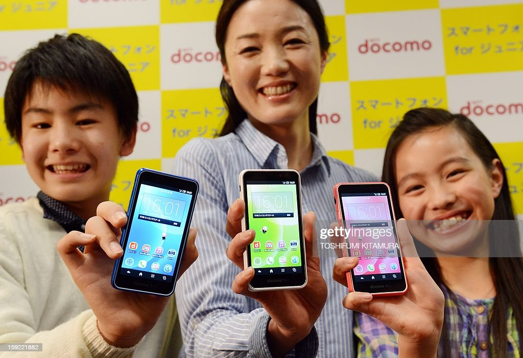 Models hold NTT DOCOMO's 'SH-05E,' the latest smartphones for juniors during its press preview in Tokyo on January 10, 2013. The water-resistant and dustproof smartphone enables parents to control voice calls and usage by setting restrictions on time of day, maximum amount of call time, as well as email and online activity.