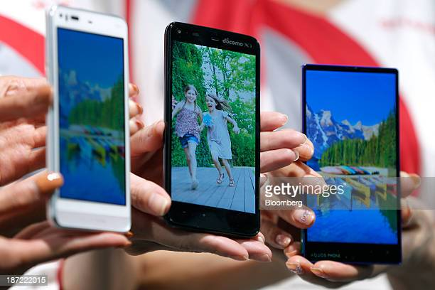 Models hold Sharp Corp smartphones the Aquos Phone Serie SHL23 for KDDI Corp's 'au' brand that features the indium gallium zinc oxide display from...