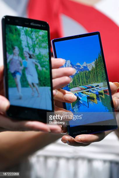 Models hold Sharp Corp smartphones the Aquos Phone Xx 302SH for SoftBank Corp that features the company's narrow frame structure 'Edgest' right and...