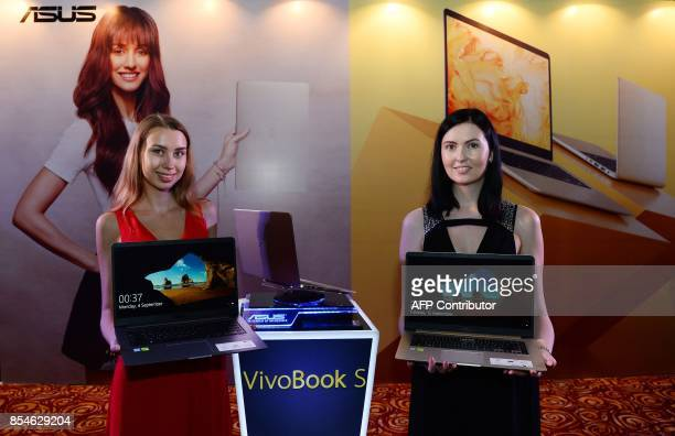 Models hold the newly launched ASUS notebooks during a promotional event in New Delhi on September 27 2017 The Taiwanese manufacturer Asus unveiled...