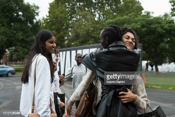 Models hug and say goodbye outside the Royal Exhibition Building on March 13 2020 in Melbourne Australia Melbourne Fashion Festival organisers...