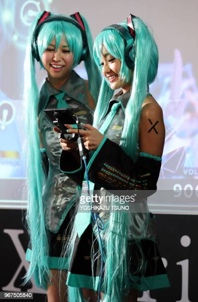 Models in costume of Hatsune Miku plays videogame with Sony's Xperia smartphone at the annual Tokyo Game Show in Chiba suburban Tokyo on Thursday...