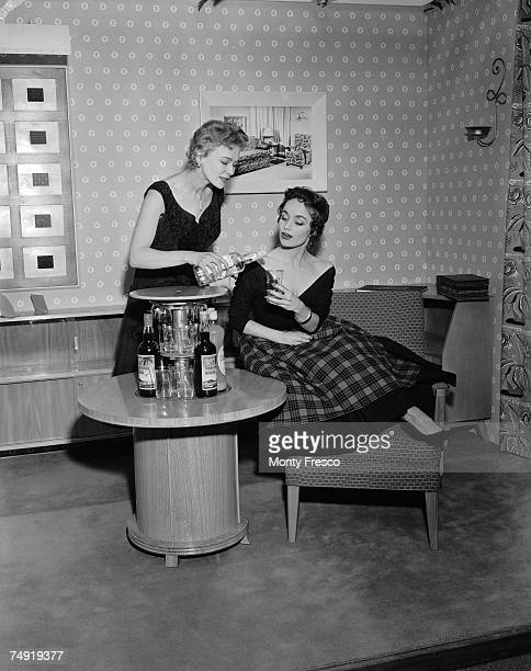 Models Jean Evans and Lynne Kennedy demostrating the push button cocktail cabinet at the British Furniture Exhibition at Earl's Court London 15th...