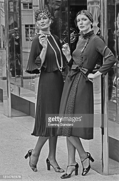 Models Jenny Keylock and Rosemary Turnbull wearing knee-length dresses and close-fitting caps, UK, 10th July 1974.