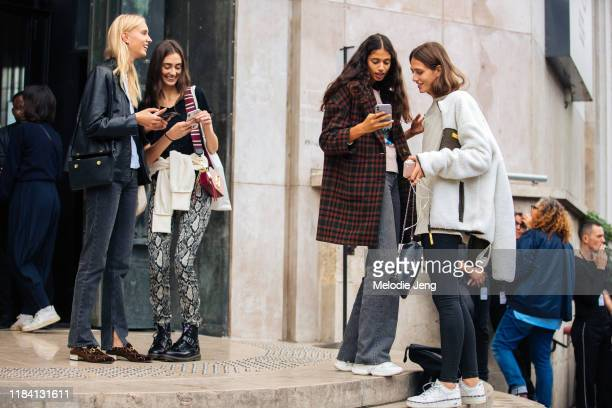 Models Jessie Bloemendaal, Amanda Googe, and Malika el Maslouhi check their phones after the Atlein show during Paris Fashion Week Spring/Summer 2020...