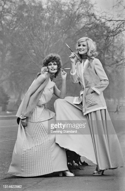 Models Karen and Jane wearing full length skirts and using elegant cigarette holders, UK, 5th April 1974.