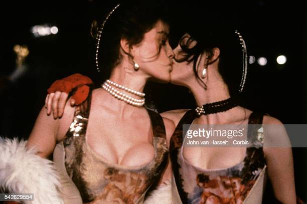 Models kiss as they wear outfits during a fashion show by British designer Vivienne Westwood.