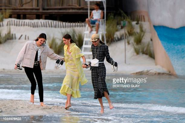 Models laugh and walk on the sand as they present creations by Chanel at the end of the SpringSummer 2019 ReadytoWear collection fashion show at the...