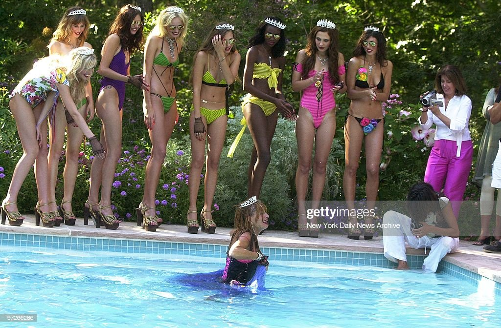 Models laugh as Betsey Johnson wades out of a swimming pool : News Photo