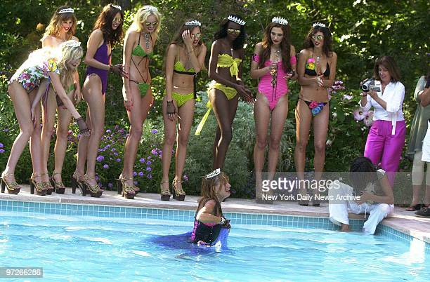 Models laugh as Betsey Johnson wades out of a swimming pool after leaping in at the end of a fashion show featuring her Spring 2003 hippieinspired...