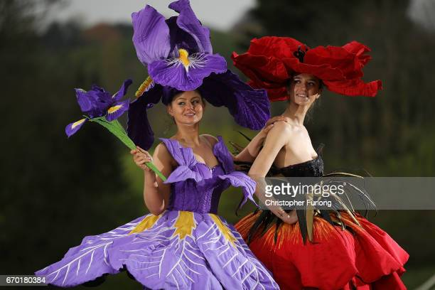 Models Lauren Green and Abi Moore pose for photographers as they wear an Iris and Poppy flower gowns designed by New Zealand artist Jenny Gillies on...