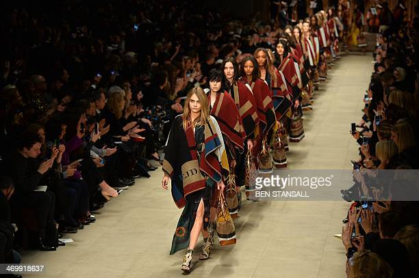 Models led by Cara Delevingne present creations from designer Burberry Prorsum during the 2014 Autumn / Winter London Fashion Week in London on...