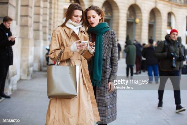 Models Lena Hardt and Maria Zakrzewska check their phone on February 28, 2018 in Paris, France. Lena wears a tan Lemaire trenchcoat, oversized white...