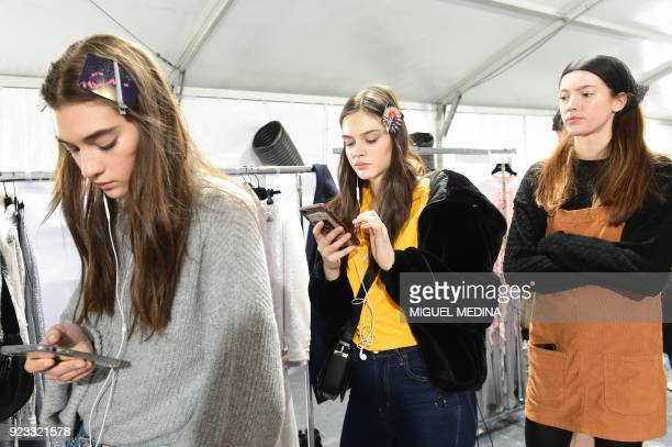 Models look at their mobile phones backstage prior to the women's Fall/Winter 2018/2019 collection fashion show by Blumarine in Milan on February 23...