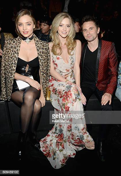 Models Miranda Kerr in Saint Laurent by Hedi Slimane Elle Evans and recording artist Matt Bellamy of Muse in Saint Laurent by Hedi Slimane attend...